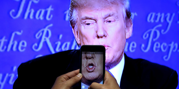 A journalist records a video from screen as Republican U.S. presidential nominee Donald Trump speaks during the first presidential debate with U.S. Democratic presidential candidate Hillary Clinton at Hofstra University in Hempstead, New York, U.S., September 26, 2016. REUTERS/Carlos Barria