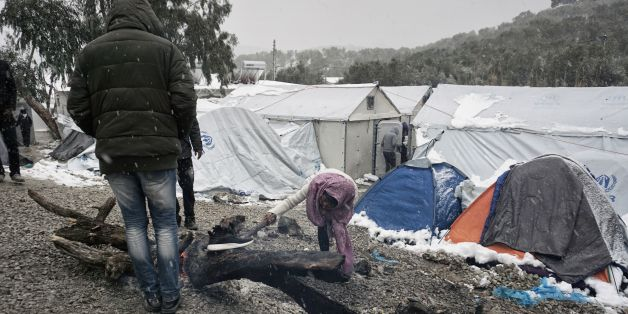 Migrants try to light a fire  during snowfall at the Moria hotspot on the Greek island of Lesbos, on January 9, 2017.