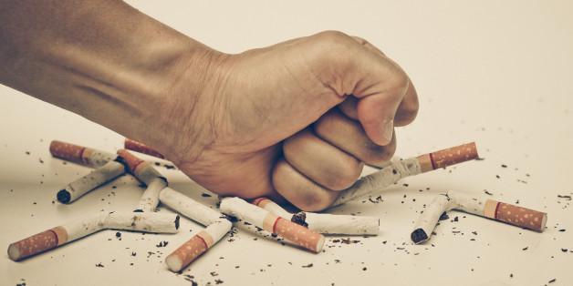 male hand destroying cigartees - stop smoking concept