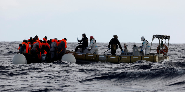 Italian Navy personnel rescues migrants from their overcrowded raft, as lifeguards from the Spanish NGO Proactiva Open Arms rescue all 112 on aboard, including two pregnant women and five children, as it drifts out of control in the central Mediterranean Sea, some 36 nautical miles off the Libyan coast January 2, 2017. REUTERS/Yannis Behrakis