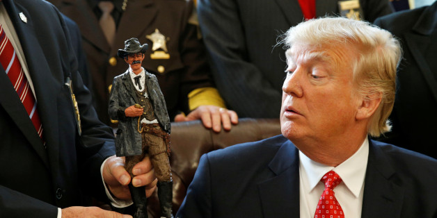 U.S. President Donald Trump receives a figurine of a sheriff during a meeting with county sheriffs at the White House in Washington, U.S. February 7, 2017.  REUTERS/Kevin Lamarque      TPX IMAGES OF THE DAY