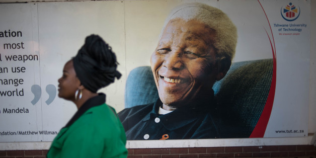 A South African woman walks in front of a poster of the late president Nelson Mandela  as she joins a march towards the Union Buildings in Pretoria on August 9, 2016 during a celebration for  Womens Day, an event marking the 60th anniversary of the 1956 women's march against the discriminatory pass laws, which restricted the movement of black people in the country. / AFP / MUJAHID SAFODIEN        (Photo credit should read MUJAHID SAFODIEN/AFP/Getty Images)