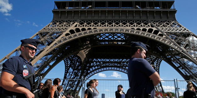 French CRS policemen patrol as tourists walk past in front of the Eiffel Tower in Paris, France August 20, 2016. REUTERS/Pascal Rossignol