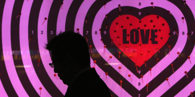 A man using his mobile phone walks past a shop window with signs advertising the upcoming Valentine's Day, at a luxury store in Tokyo January 30, 2014. Japan's core consumer prices rose 1.3 percent in December from a year earlier, the fastest pace in more than five years, adding to evidence the economy is making steady progress towards ending 15 years of grinding deflation. Picture taken January 30, 2014. REUTERS/Yuya Shino (JAPAN - Tags: BUSINESS)