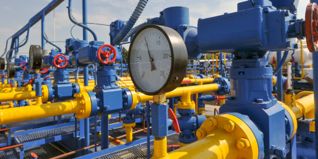 Pressure meter and red faucet with steel yellow pipe in natural gas treatment plant in bright sunny summer day