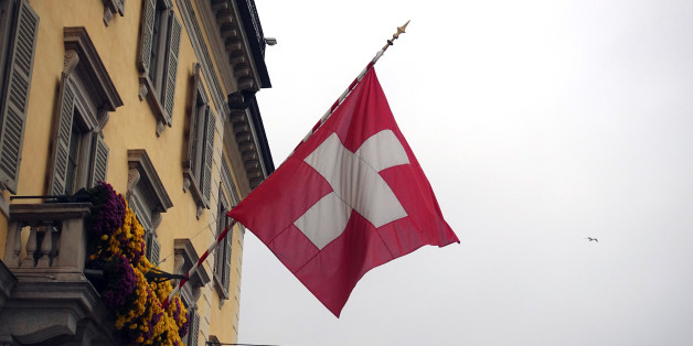 A Swiss national flag flies on the side of a residential building in Lugano, Switzerland, on Tuesday, Nov. 15, 2016. While the Swiss National Bank (SNB) admitted to interventions to weaken the franc following the Brexit referendum, it declined to comment after the U.S. election last week. Photographer: Stephen Kelly/Bloomberg via Getty Images