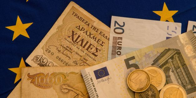 A picture taken on June 29, 2015 in Lille shows Drachma bills, Greece's former currency, next to euro bills and coins. The European single currency briefly dropped below $1.1 today as investors grow concerned Greece is headed for a debt default and a possible eurozone exit. AFP PHOTO / DENIS CHARLET        (Photo credit should read DENIS CHARLET/AFP/Getty Images)