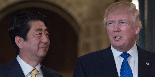US President Donald Trump and Japanese Prime Minister Shinzo Abe pose for photos at Trump's Mar-a-Lago resort in Palm Beach, Florida, on February 11, 2017 prior to dinner. / AFP / NICHOLAS KAMM        (Photo credit should read NICHOLAS KAMM/AFP/Getty Images)