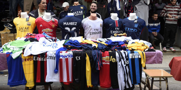 An Algerian vendor displays shirts of football players at a market on February 18, 2016 in the old part of the capital Algiers, known as the Casbah.   English club Leicester City's midfielder, Riyad Mahrez shirts are flying off the shelves of sports shops in Algiers as the Algerian winger continues to impress for Premier League leaders Leicester City. / AFP / Farouk Batiche        (Photo credit should read FAROUK BATICHE/AFP/Getty Images)