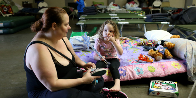 Jennifer Moss (L), of Marysville, ties her daughter Kaylin's shoes at the Salvation Army relief center at the Placer County Fair Grounds in Roseville, California, after an evacuation was ordered for communities downstream from the Lake Oroville Dam, in Oroville, California, U.S. February 14, 2017.  REUTERS/Beck Diefenbach