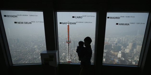 "A man holds his baby while viewing central Seoul shrouded in heavy haze at an observation platform at ""N Seoul Tower"" located atop Mt. Namsan in central Seoul February 27, 2014. High-level fine dust and smog continued to pollute the air of Seoul and its metropolitan region in South Korea on Thursday. Seoul city authorities asked that residents refrain from doing outdoor activities due to the worsening air quality, according to local media.  REUTERS/Kim Hong-Ji (SOUTH KOREA - Tags: ENVIRONMENT TR"
