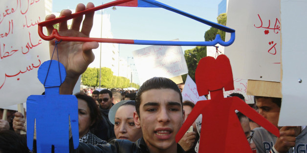 A protester holds a makeshift sign representing men and women during a protest in Tunis January 29, 2011. The protesters are calling for equality between men and women. REUTERS/Louafi Larbi (TUNISIA - Tags: POLITICS CIVIL UNREST SOCIETY)