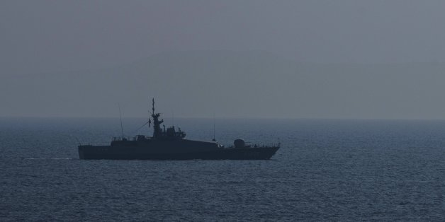 A Turkish warship and a coast guard helicopter patrol the egean sea between Turkish coast and Lesbos island on March 21, 2016 at Kucukkuyu district in Canakkale western Turkey.  