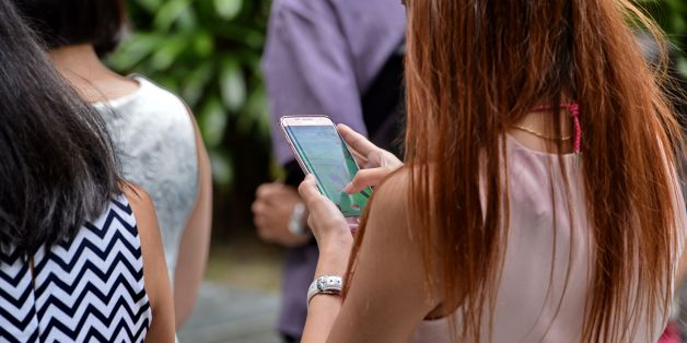 A woman plays Pokemon Go while walking along the pavement in Singapore on August 11, 2016.Pokemon Go was available in nine countries on August 6, including Singapore. / AFP / ROSLAN RAHMAN        (Photo credit should read ROSLAN RAHMAN/AFP/Getty Images)