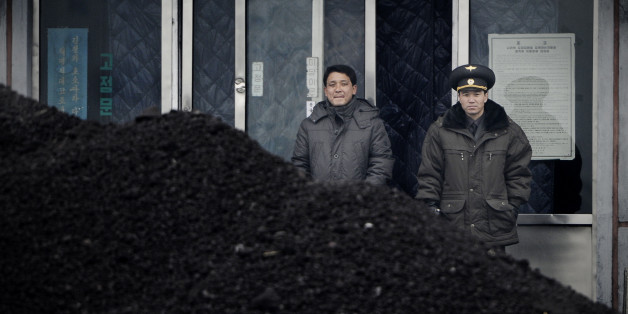 This picture taken on December 14, 2012 from China's northeastern city of Dandong, looking across the border, shows a North Korean military officer (R) and a North Korea man (L) standing behind a pile of coal along the banks of the Yalu River in the northeast of the North Korean border town of Siniuju.  China is North Korea's biggest trading partner by far, and most of the business passes through Dandong in northeastern China, where lorries piled high with tyres and sacks are processed at the cu