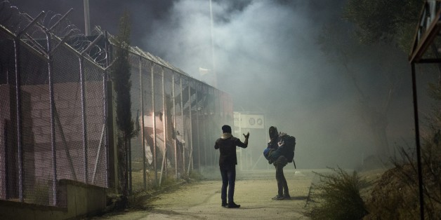 LESBOS ISLAND, GREECE - NOVEMBER 25: Refugees are seen as firefighters try to extinguish the fire at the Moria refugee camp in the island of Lesbos, Greece on on November 25, 2016. At least 2 refugees dead and 2 other wounded after a fire broke our following an explosion. (Photo by Claire Thomas/Anadolu Agency/Getty Images)
