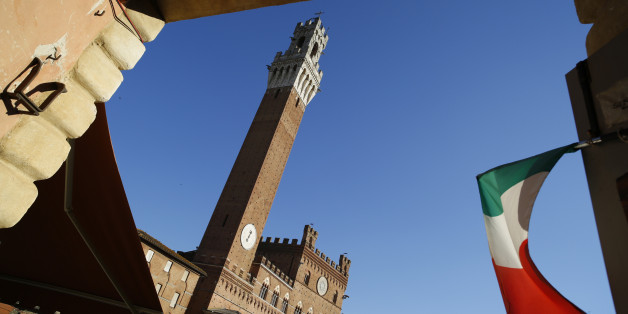 The Italian national flag flies in an entrance to the Piazza del Campo with the Torre del Mangia in the distance, in Siena, Italy, on Friday, Aug. 5, 2016. Banca Monte dei Paschi di Siena SpA's plan to offload $31 billion in doubtful loans, designed to attract investors to a share sale by reducing the bank's risk of losses, will still leave it with a bad-debt level considered unsafe by industry standards. Photographer: Marc Hill/Bloomberg via Getty Images