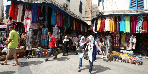 People walk past a clothes shop in souk of the old quarter in Tunis, Tunisia, August 10, 2016. REUTERS/Zoubeir Souissi