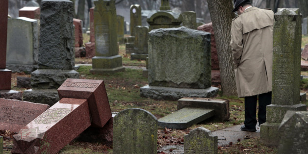People walk through toppled graves at Chesed Shel Emeth Cemetery in University City on Tuesday, Feb. 21, 2017 where almost 200 gravestones were vandalized over the weekend. (Robert Cohen/St. Louis Post-Dispatch/TNS via Getty Images)