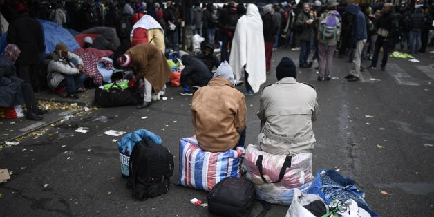 Migrant wait during the evacuation of a makeshift camp near Stalingrad metro station in Paris on November 4, 2016, one of several camps sprouting up around the French capital. Over 2000 migrants were moved by police from the Paris town center to a legal migrant camp. / AFP / LIONEL BONAVENTURE        (Photo credit should read LIONEL BONAVENTURE/AFP/Getty Images)