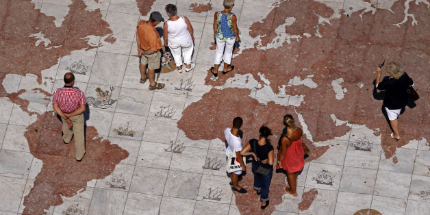 People walk over a world map engraved in marble in Lisbon September 14, 2011. Global markets have been roiled since the end of July by the twin fears of a recession in the United States and Europe's protracted debt woes, which have forced Greece, Ireland and Portugal to take bailouts and piled bond market pressure on Italy and Spain. REUTERS/Jose Manuel Ribeiro (PORTUGAL - Tags: POLITICS BUSINESS)