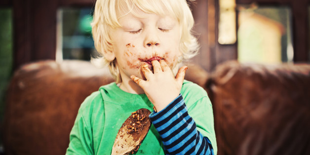 Little boy licking chocolate off his fingers and wooden spoon while making cakes.