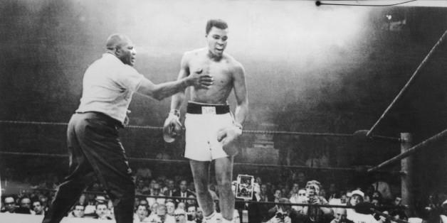 Photo prise le 26 mai 1965 à Lewiston, aux Etats-Unis, lors du championnat du monde de boxe des poids lourds au cours duquel le boxeur américain Mohamed Ali (Cassius Clay) (C) a conservé son titre de champion de monde en battant Sonny Liston (au sol) par K.O au premier round après une minute d'un combat arbitré par Joe Walcott (G).A picture taken May 26, 1965, in Lewiston, USA, during the world heavyweight boxing championship, at the end of which the American Muhammad Ali (Cassius