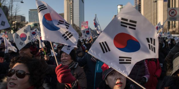 Pro-government activists shout slogans and wave flags as they stage a rally in central Seoul on February 25, 2017.South Korea's Constitutional Court will hold its final impeachment hearing to rule on the fate of President Park Geun-Hye at the end of the month, Yonhap News Agency reported February 22. / AFP / Ed JONES        (Photo credit should read ED JONES/AFP/Getty Images)