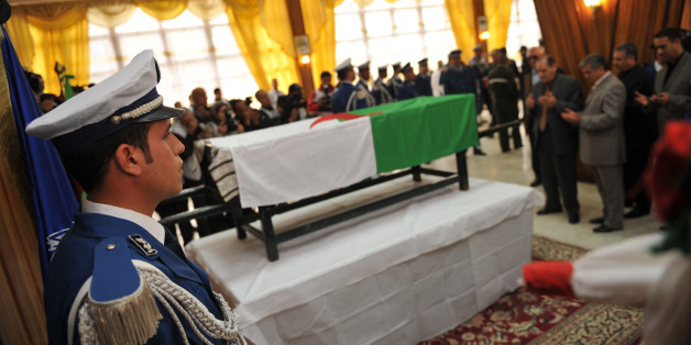Algerian policeman stands guard as relatives pay respects to the flag-draped coffin of Algeria's police chief Ali Tounsi at a ceremony to pay the last tribute at the police training academy, on February 26, 2010 in Algiers. Tounsi was shot dead Thursday during a blazing row with a subordinate in his office at police headquarters in central Algiers. AFP PHOTO / FAYEZ NURELDINE (Photo credit should read FAYEZ NURELDINE/AFP/Getty Images)