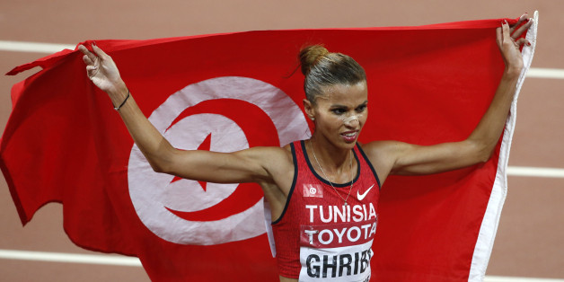 Habiba Ghribi of Tunisia holds her national flag after finishing second in the women's 3000 metres steeplechase final at the IAAF World Championships at the National Stadium in Beijing, China August 26, 2015. REUTERS/Kim Kyung-Hoon
