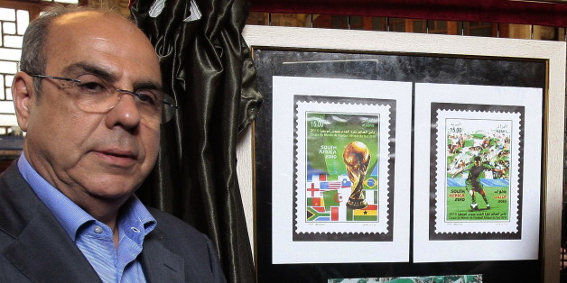 President of the Algerian Football Federation (FAF) Mohamed Raouraoua poses for a picture near new released stamps displayed at the 'Grande Poste' in Algiers, on May 5, 2010. Algerian post authorities released a new range of stamps represnting the National football team that taking place in the World Cup 2010 in South Africa.      AFP PHOTO / STR (Photo credit should read STR/AFP/Getty Images)