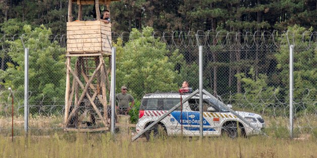 Kelebija, Serbia - September 10, 2016: Hungarian policemen watching the Serbia Hungarian border fence. This border wall was built in 2015 in order to stop the incoming refugees & migrants passing through Serbia and the Balkans Route.