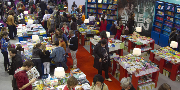 Visitors to the Paris Book Fair look at children's books on display on the opening day of the four-day event in Paris, March 16, 2012.  REUTERS/Charles Platiau (FRANCE - Tags: SOCIETY)