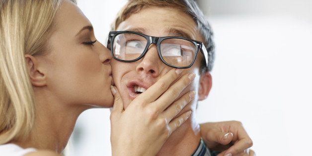 Beautiful blonde kissing male geek on the cheek while male looks alarmed and looks sideways