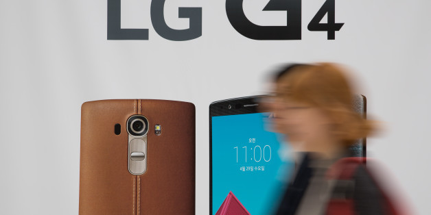 People walk past an advertisement for LG Electronics Inc.'s G4 smartphone at a promotional booth in the COEX mall in Seoul, South Korea, on Wednesday, April 29, 2015. LG, South Korea's second biggest phone maker, unveiled the leather-clad G4 smartphone, the brand's new flagship, in a bid to cement its luxe status. Photographer: SeongJoon Cho/Bloomberg via Getty Images