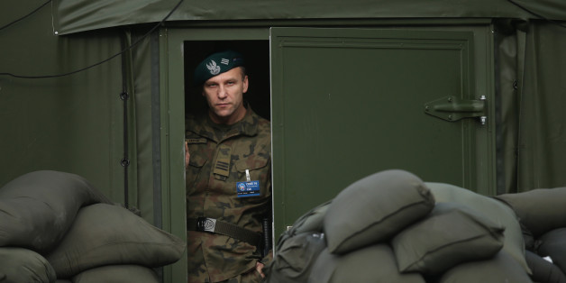 SZCZECIN, POLAND - NOVEMBER 28:  A Polish soldier peeks froma tent during the visit of Polish President Andrzej Duda and German President Joachim Gauck at the headquarters of the NATO Multinational Corps Northeast on November 28, 2016 in Szczecin, Poland. Soldiers from 23 NATO countries as well as Sweden and Finland take part in the Corps, which spearheads NATO's Very High Readiness Joint Task Force.  (Photo by Sean Gallup/Getty Images)