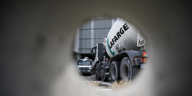 A concrete mixing truck is seen through a hole in a wall at Lafarge concrete production plant in Pantin, outside Paris, April 7, 2014. Switzerland's Holcim unveiled a deal to buy France's Lafarge on Monday to create the world's biggest cement maker, with $44 billion of annual sales, and spark a raft of asset sales worldwide to steer it through antitrust rules.  REUTERS/Christian Hartmann (FRANCE - Tags: BUSINESS CONSTRUCTION)