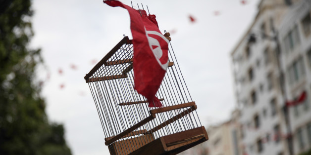 TUNIS, TUNISIA – JANUARY 14: An empty cage of bird decorated with a Tunisian flag is seen raised during a march held on avenue Habib Bourguiba in the capital Tunis, to celebrate Revolution Day, the six-year anniversary of the overthrow of the 23-year dictator President Ben Ali. (Photo by Chedly Ben Ibrahim/Corbis via Getty Images)