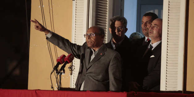 Moncef Marzouki greets supporters from his party's headquarters' balcony in Tunis December 23, 2014. Beji Caid Essebsi beat rival and incumbent Marzouki with 55.68 percent of the vote against 44.32 percent in Sunday's run-off ballot between the two men, according the results released on Monday by the electoral authorities. REUTERS/Zoubeir Souissi (TUNISIA - Tags: ELECTIONS POLITICS)