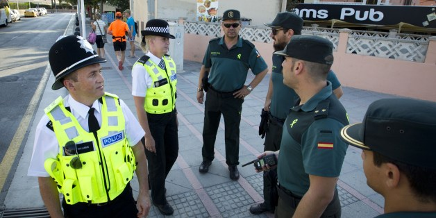 British police officers, popularly known as 'bobbies' walk Spanish Civil Guards as they patrol at Punta Ballena street in the holiday resort of Magaluf in Calvia on Mallorca Island on August 11, 2015.Two  'bobbies', a man and a woman who speak Spanish, patrolled today morning with the Spanish Guardia Civil  in Magaluf, a Majorca beach in the Spanish Balearic archipelago, where the British holidaymakers' alcohol and sex excesses are scandalous. AFP PHOTO / JAIME REINA        (Photo credit should