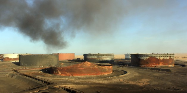 A picture taken on January 8, 2016 showssmoke billowing from a petroleum storage tank after a fire was extinguished at Al-Sidra oil terminal, near Ras Lanuf in the so-called 'oil crescent' along Libya's northern coast. At least four petroleum storage tanks were set ablaze during deadly fighting as the Islamic State group tries to seize coastal export terminals in eastern Libya, the National Oil Company said.  / AFP / STRINGER        (Photo credit should read STRINGER/AFP/Getty Images)