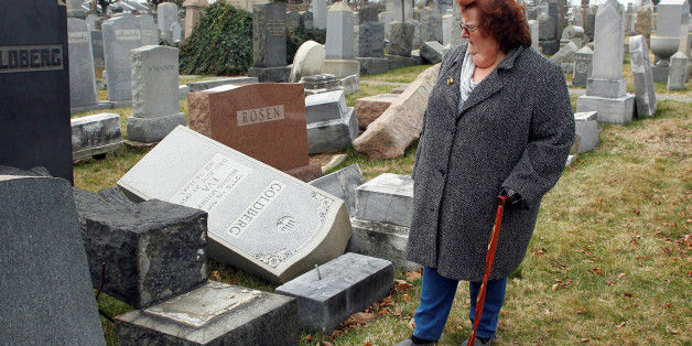 Judy Pogachefsky looks at headstones pushed off their bases by vandals in the Mount Carmel Cemetery, a Jewish cemetery, in Philadelphia, Pennsylvania, U.S. February 27, 2017. Pogachefsky's grandparents are buried in the cemetery and she was trying to locate their grave. REUTERS/Tom Mihalek