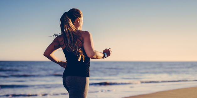 Long blond haired woman jogging at beach with smartwatch into sunlight.