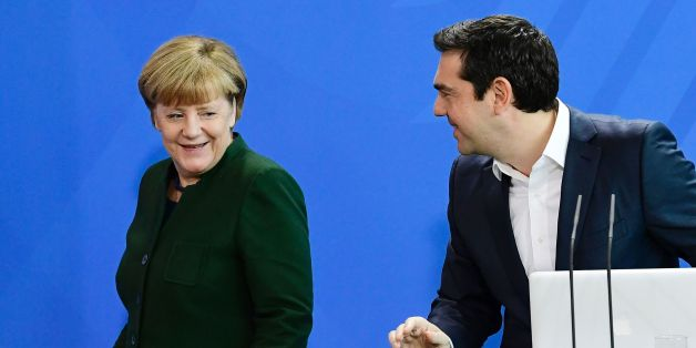 German Chancellor Angela Merkel (L) passes by Greek Prime Minister Alexis Tsipras after delivering a statement ahead talks focused on the refugee crisis, Cyprus, Turkey and Athens' debt woes in Berlin, on December 16, 2016. / AFP / TOBIAS SCHWARZ        (Photo credit should read TOBIAS SCHWARZ/AFP/Getty Images)