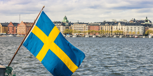 Stockholm view to downtown with a Swedish flag on the waterfront.