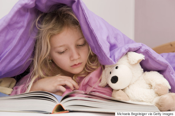child reading with stuffed animal