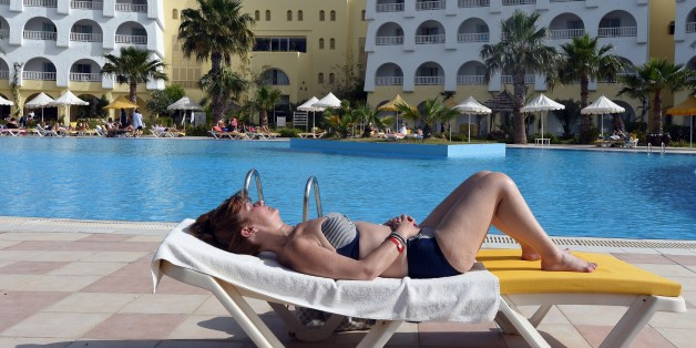 A tourist sunbathes at a hotel on May 17, 2014 on the Mediterranean resort island of Djerba. AFP PHOTO / FETHI BELAID        (Photo credit should read FETHI BELAID/AFP/Getty Images)