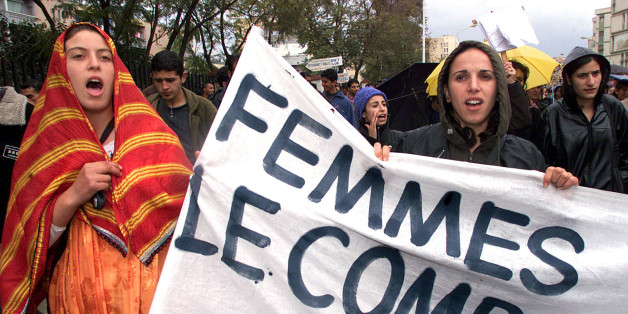 "Algerian women hold a banner reading ""Women, the Fight"", as they march in Algiers to demand the repeal of the Algerian family laws (code de la famille) March 7, 2002. The demonstration was organised on the eve of  International Women's Day."