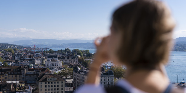 Zurich, Switzerland - 30 September 2016: A female tourist is taking pictures of Zurich from the observation deck on top of Grossmunster cathedral.
