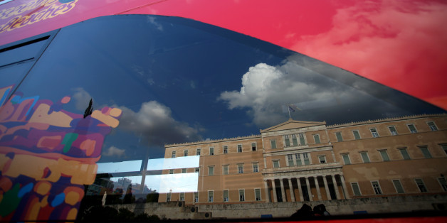 The Greek Parliament reflected on a touristic bus showing the Parthenon in Athens, May 18, 2016 (Photo by Giorgos Georgiou/NurPhoto via Getty Images)